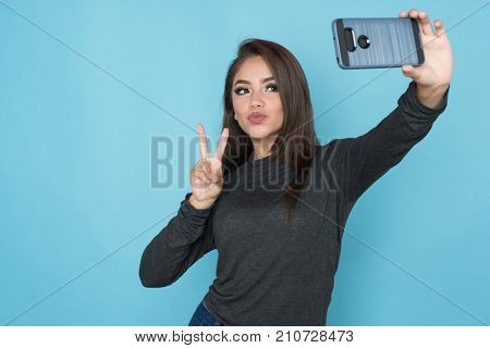 Hispanic girl taking a selfie with her phone