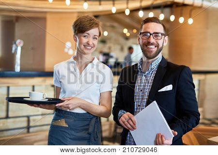 Group portrait of cheerful bearded restaurant manager and pretty waitress posing for photography while standing against bar counter