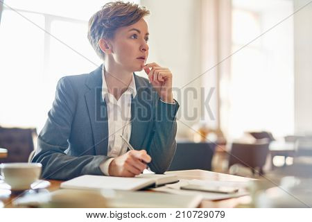 Waist-up portrait of confident businesswoman taking necessary notes while thinking over promising project, interior of modern coffeehouse on background