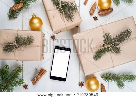 Christmas background with mobile phone with blank white screen gifts fir branches cones cinnamon on wooden background copy space. Flat lay top view. Christmas application mock up template