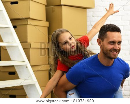 Dad And Daughter Pretend To Fly By Pile Of Boxes