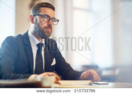 Portrait of handsome bearded white collar worker looking away pensively while working on promising project at modern office
