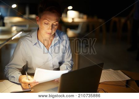 Professional accountant reading financial document late in the office