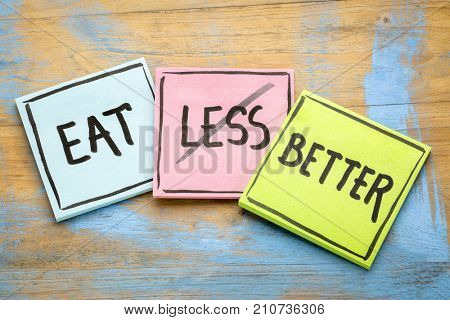 eat better (not less) - healthy eating concept - handwriting on sticky notes against grunge wood