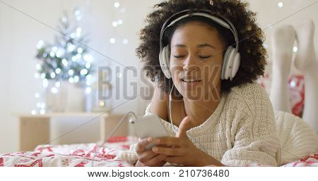 Attractive young lady in long white knit sweater on bed listening to music on her mp3 player with cord in mouth