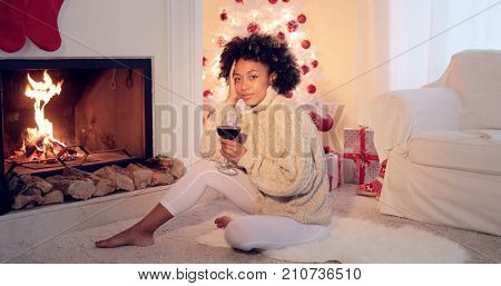 Woman in leggings and sweater sits by white christmas tree with presents under it. She holding glass of red wine  wearing cozy woolen sweater.