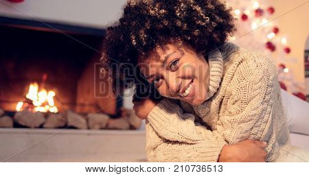 Lovely black woman in sweater and leggings lays seductively on rug beside fireplace and christmas tree
