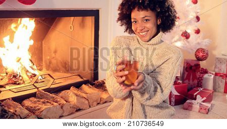 Happy young woman relaxing at Christmas with a mug of hot spicy lemon tea as she sits on the floor in front of the fire with a pile of gifts and decorated tree behind.