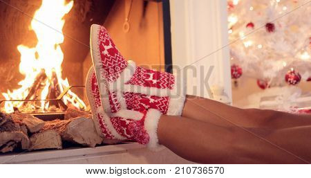 Young woman relaxing in festive red and white Christmas booties with her feet to a blazing fire in a hearth  close up view