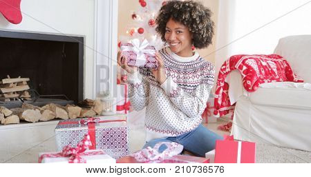 Pretty happy young woman checking her Christmas gifts on the floor in her living room holding up a decorative box tied with a bow with friendly smile.