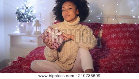 Single beautiful African woman with calm or cautious expression holding Christmas gift in bed