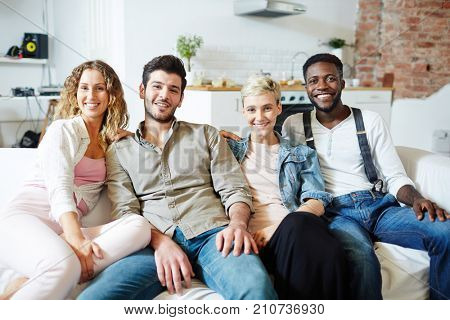 Two young restful couples sitting on sofa while gathering after work or on weekend