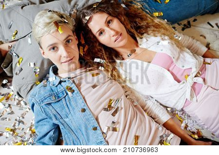 Friendly girls in casualwear covered by confetti lying on male chest at party