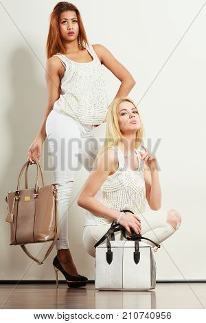 Fashion concept. Two women mulatto and blonde caucasian female in white fashionable clothes high heels shoes with bags handbags.