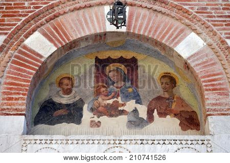 LUCCA, ITALY - JUNE 03: Virgin Mary with baby Jesus and Saints, lunette over the entrance door to the Sant Anastasio church in Lucca, Tuscany, Italy on June 03, 2017.