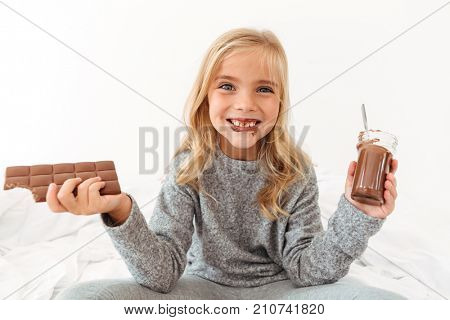 Cute funny girl holding chocolate bar and showing her dirty teeth, looking at camera