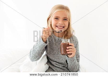 Happy blonde girl in gray pajamas holding glass jar and spoon with chocolate spread, looking at camera