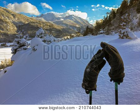Gray thick winter gloves on hiking trekking sticks on fresh snow with blurred mountains and blue background, winter in Austria, Europe
