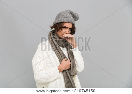 Portrait of an unsatisfied frozen girl in scarf and hat holding hand at her face and looking at camera isolated over gray background