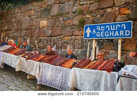GEGHARD, ARMENIA - OCTOBER 1, 2016: Local people sell armenian home made traditional sweets made from dried fruits at the market near the ancient temple of Geghard, Armenia. out of focus image