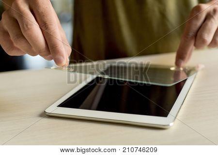 closeup of a young caucasian man installing a screen protector in a digital tablet