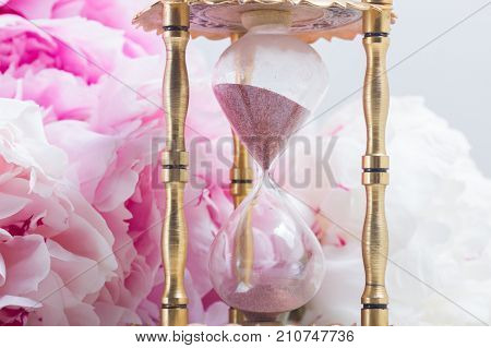 Hour glass and fresh peony flowers on white leather background
