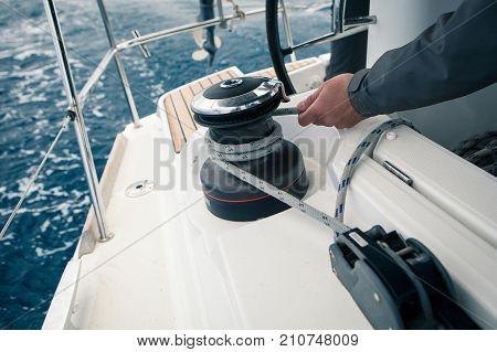 Sailor pulling rope, outdoor activities, sailboat sport race, man in action