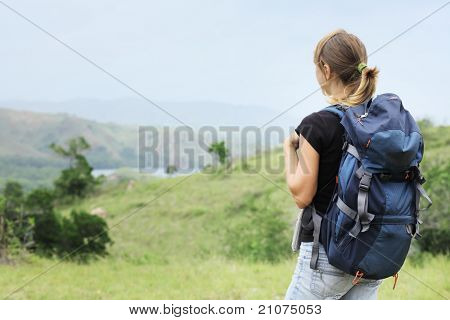 Young woman with backpack walking through a wild territory