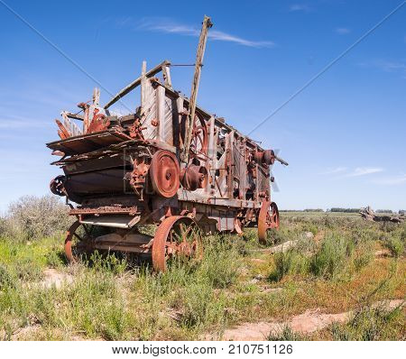 Antique threshing machine sits in a field on a farm in South Africa
