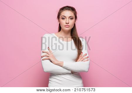 The young woman's portrait with proud and arrogant emotions at studio against pink