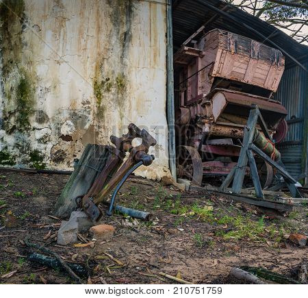 An antique threshing machine sits in a derelict barn on a farm in South Africa