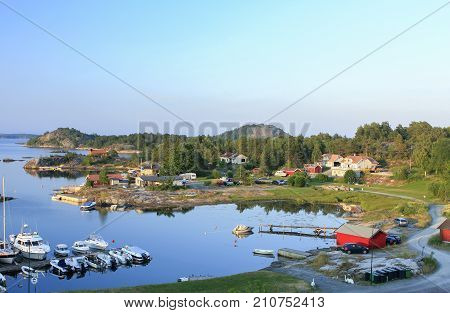 KRISTIANSAND ARCHIPELAGO, NORWAY ON JULY 01. View over bridges, boats and lodges by a little harbor on July 01, 2009 in Kristiansand archipelago, Norway. Calm summer evening. Editorial use.
