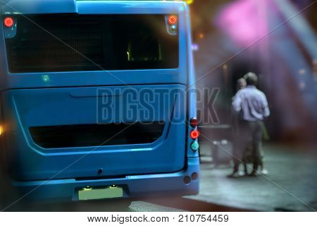 A bus on a bus stop is going to leave. Two men are waiting for the bus. Night in a city. Concept of transport in the night city, safety.