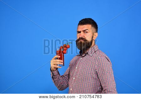 Man With Beard Holds Tomato Juice On Blue Background