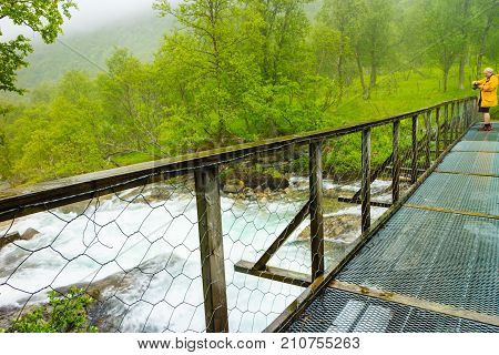 Tourist With Camera On River Bridge, Norway