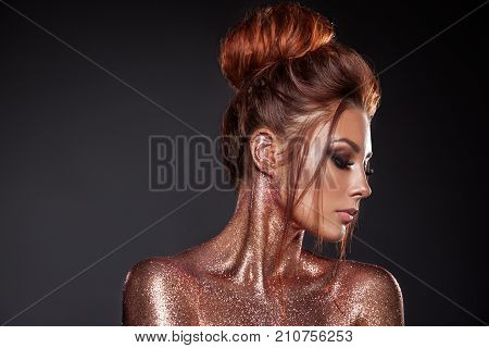 Portrait of a young beautiful girl with gold and bronze sparkles. Hairstyle of red hair clean tanned skin beautiful bright makeup pink lipstick on lips. Beauty of the face model.