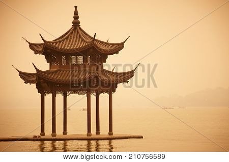 Chinese traditional wooden gazebo on the coast of West Lake, public park in Hangzhou city, China.