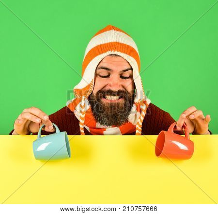 Coffee Time. Man With Beard Holds Orange And Blue Cups.