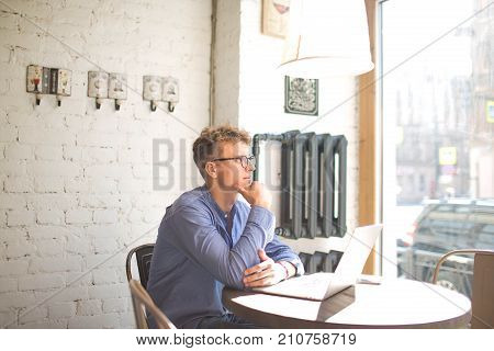 Young man in glasses freelance content writer thinks about new ideas, siting with laptop computer in coffee shop. Thoughtful male marketing coordinator watching in cafe window during work on net-book
