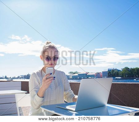 Woman freelancer chatting on mobile phone during work on laptop computer, sitting outdoors in sunny day. Pretty female student using cell telephone and portable net-book, resting near embankment river
