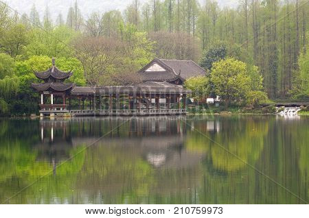 Chinese traditional bridge with pavilion on the coast of West Lake, public park in Hangzhou city, China.