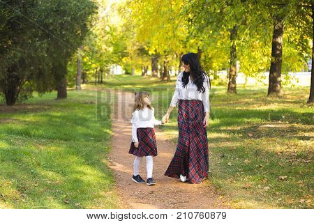 Mother And Daughter Walking In The Park And Enjoying The Beautifu Nature