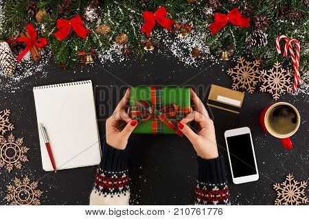 Getting online delivery of christmas gift. Woman holding holiday present, wish list, credit card and smartphone on table with xmas decoration, top view, copy space