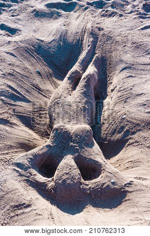 back perspective of romantic and sexy sand sculpture artwork or glyph of a naked woman or mermaid lie in sand on the beach in summer in vacation