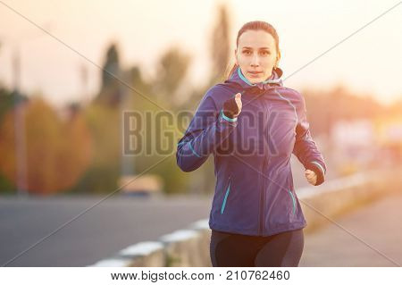 Young sporty woman jogging on bridge in the morning. Running fitness girl in sportswear outdoor image with copy space