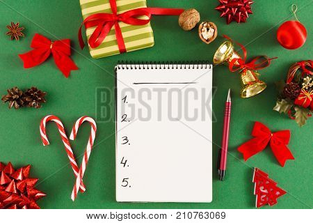 Christmas wish list or letter to Santa. Notepad with copy space on green messy table background. Preparing for winter holidays, top view