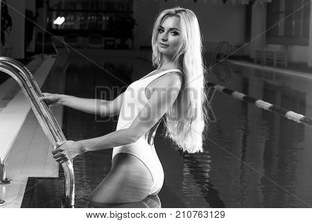 Stunning sexy blonde woman with blue eyes dressed in white deep plunge swimsuit standing against swimming pool on background, holding metallic railing and touching her long hair with hand. Side view.