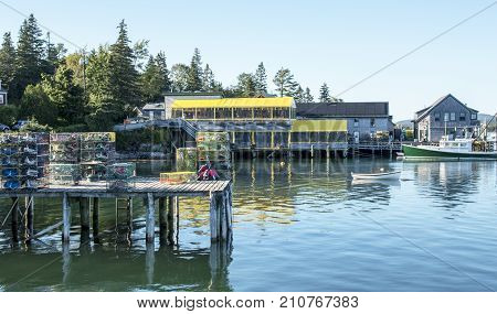 Bass Harbor Maine facing Thurstons Lobster pound with lobster traps buoys a pier and boats in the picture