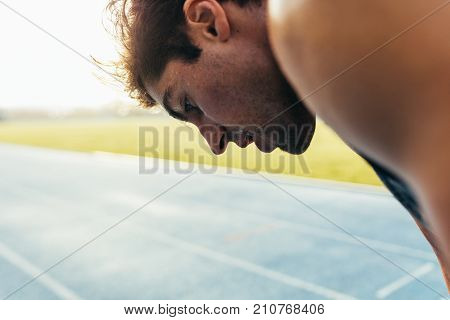 Closeup of a sprinter standing on a running track. Tired athlete relaxing after a run standing on the track. poster