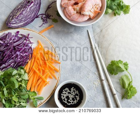 Ingredients for cooking fresh spring rolls - fresh carrots, red cabbage, corn lettuce and shrimps. Soy sauce, sesame, chopsticks on a gray background